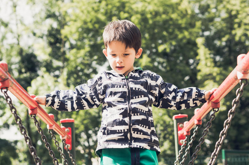 Boy and playground equipment. Boy holding on metal handrails of a climb equipment on a playground on August 2017 in Poznan, Poland in standard film look royalty free stock images