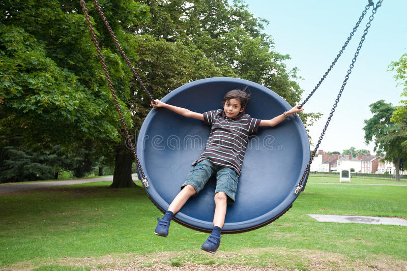 boy in playground swing stock image