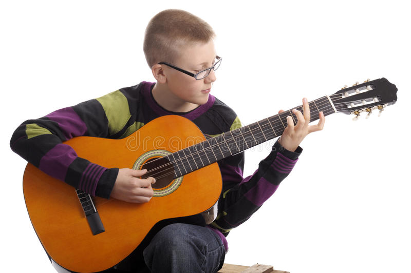 Boy playing the accoustic guitar. Isolated on white background stock photos