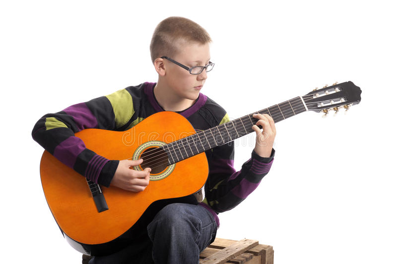 Boy playing the accoustic guitar. Isolated on white background royalty free stock images