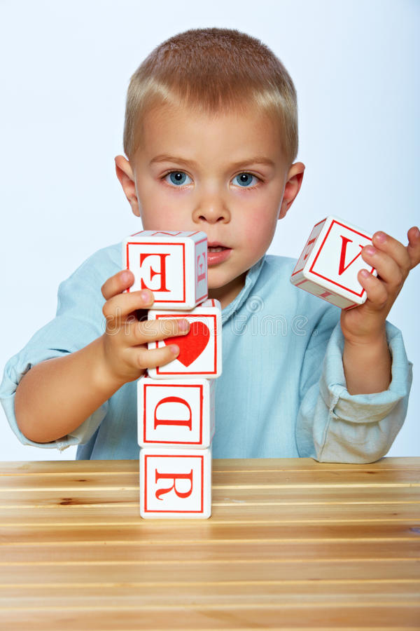 Boy playing with alphabet blocks royalty free stock photos