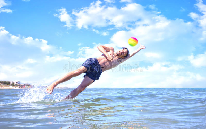 Boy playing ball in the sea stock images