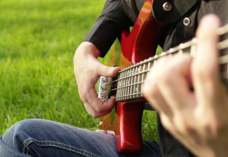 Boy playing the bass guitar. Teenage boy playing the bass guitar on the lawn stock photo