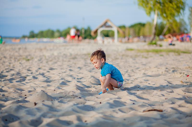 Boy playing on beach. Child play at sea on summer family vacation. Sand and water toys, sun protection for young child. Little boy. Digging sand, building royalty free stock images