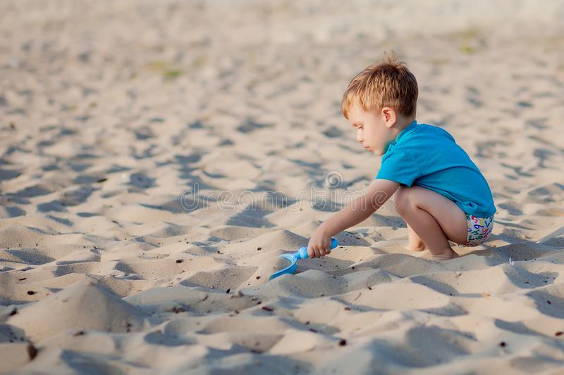 Boy playing on beach. Child play at sea on summer family vacation. Sand and water toys, sun protection for young child. Little boy royalty free stock photography