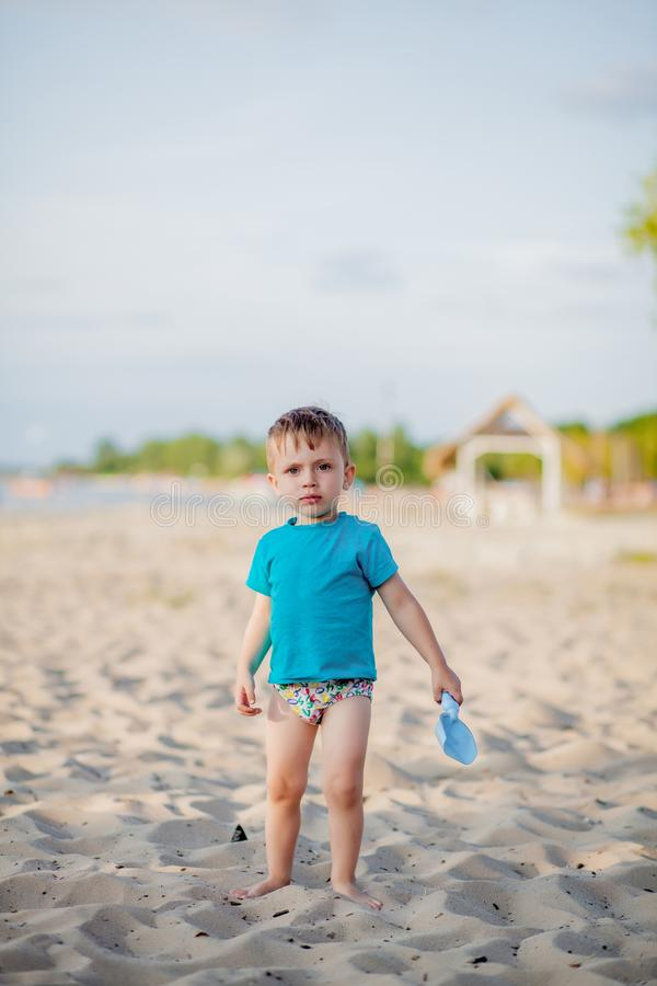 Boy playing on beach. Child play at sea on summer family vacation. Sand and water toys, sun protection for young child. Little boy. Digging sand, building royalty free stock image