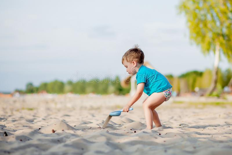 Boy playing on beach. Child play at sea on summer family vacation. Sand and water toys, sun protection for young child. Little boy. Digging sand, building royalty free stock photography