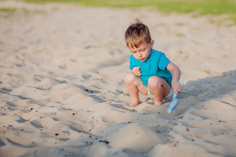 Boy playing on beach. Child play at sea on summer family vacation. Sand and water toys, sun protection for young child. Little boy. Digging sand, building stock photography