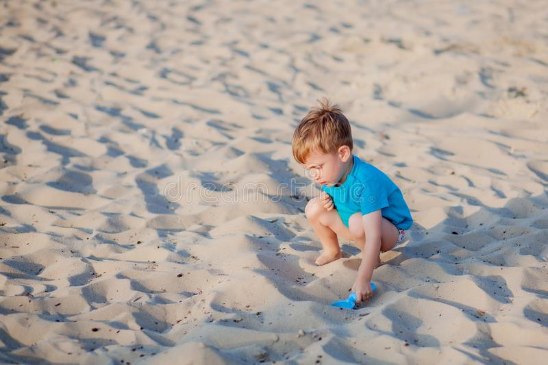Boy playing on beach. Child play at sea on summer family vacation. Sand and water toys, sun protection for young child. Little boy. Digging sand, building stock photos