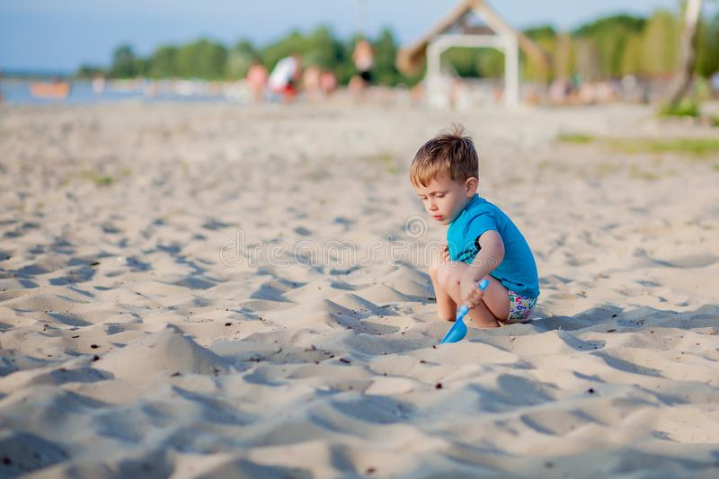 Boy playing on beach. Child play at sea on summer family vacation. Sand and water toys, sun protection for young child. Little boy. Digging sand, building stock photo