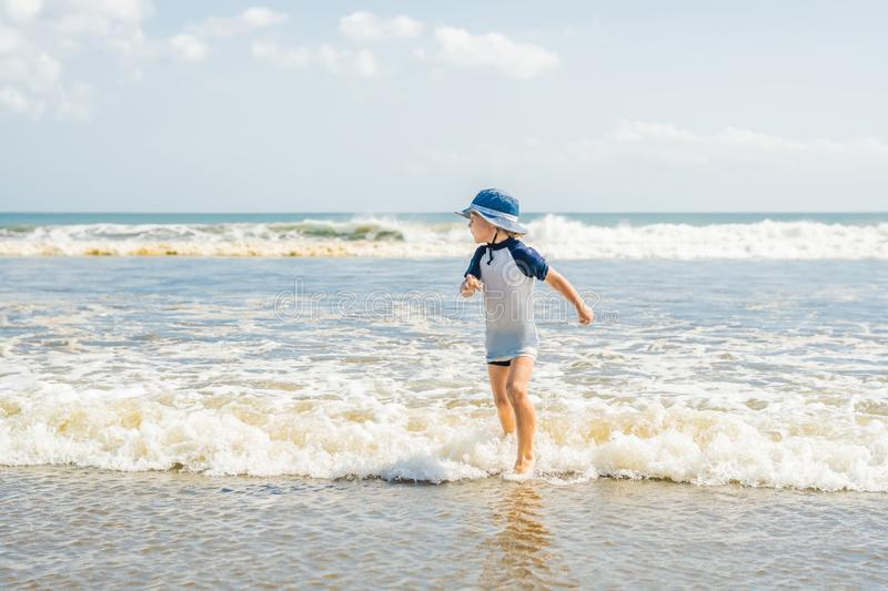 Boy playing on the beach in the water royalty free stock images