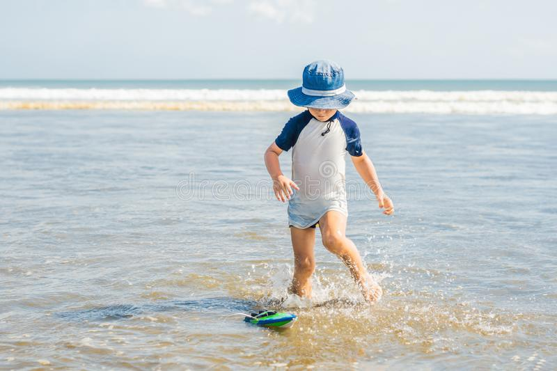 Boy playing on the beach in the water stock images
