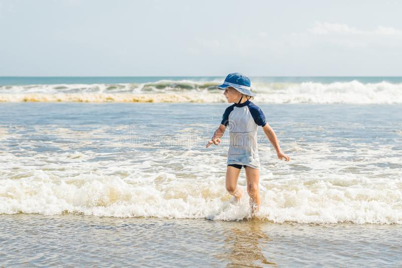 Boy playing on the beach in the water stock image