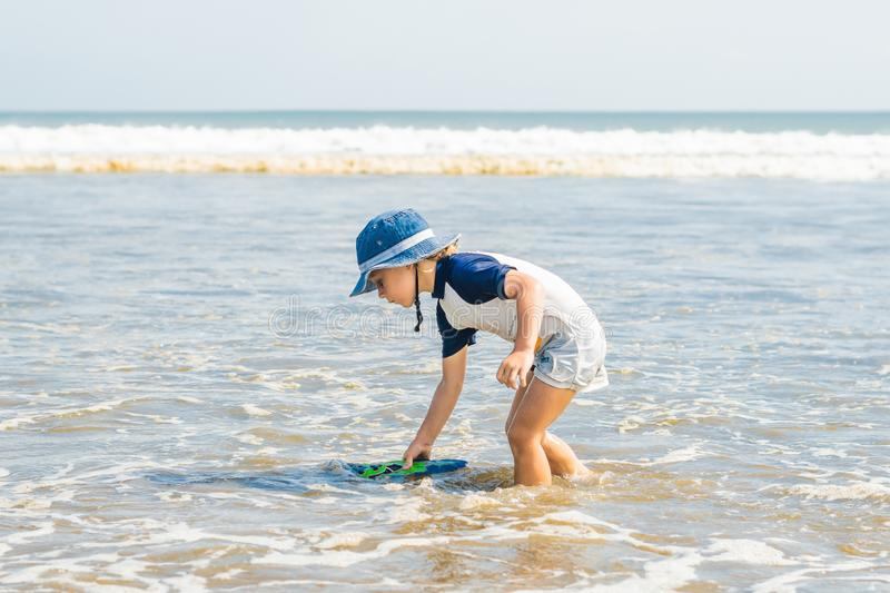Boy playing on the beach in the water royalty free stock photos