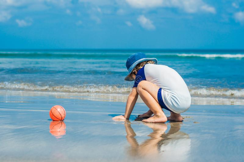 Boy playing on the beach in the water stock photography