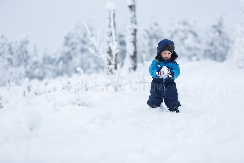 Happy caucasian child playing in snow. Boy playing in big snow in winter. Happy caucasian child playing in snow royalty free stock images
