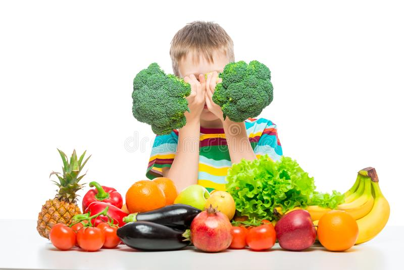 Boy playing with broccoli and a bunch of vegetables and fruits posing in the studio isolated on white royalty free stock photo