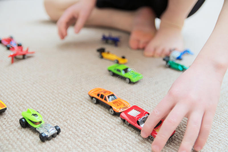 Boy playing with car collection on carpet. Child hand play. Transportation, airplane, plane and helicopter toys for children, miniature models. Many cars for royalty free stock images