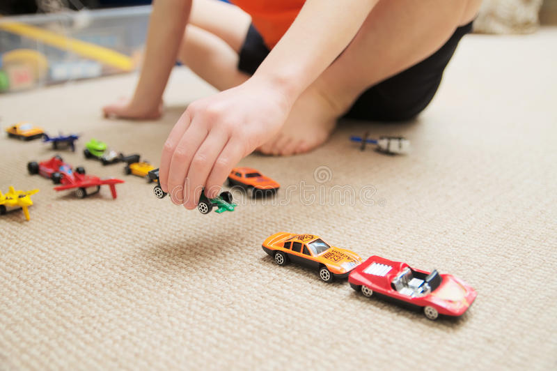 Boy playing with car collection on carpet.Child hand play. Transportation, airplane, plane and helicopter toys for children. Miniature models. Many cars for royalty free stock image