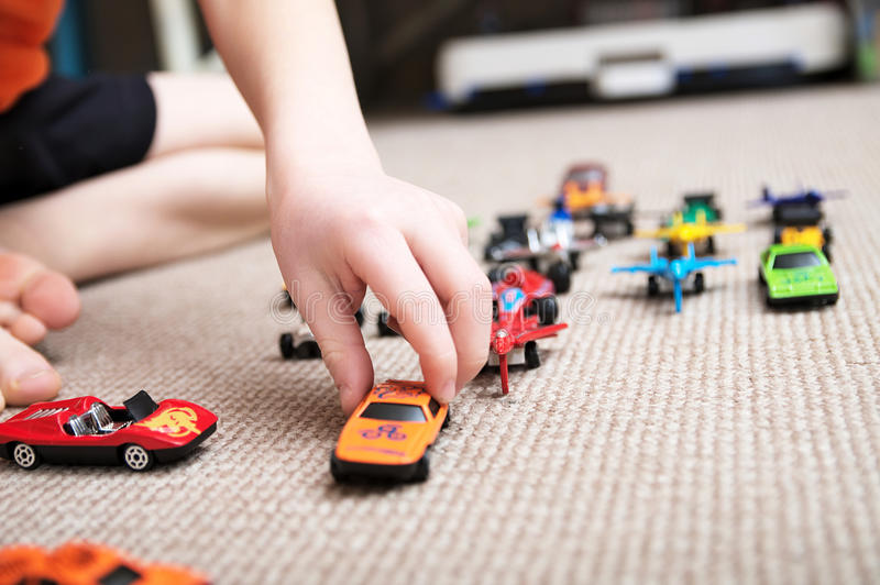 Boy playing with car collection on carpet.Child hand play. Transportation, airplane, plane and helicopter toys for children. Miniature models. Many cars for stock photo