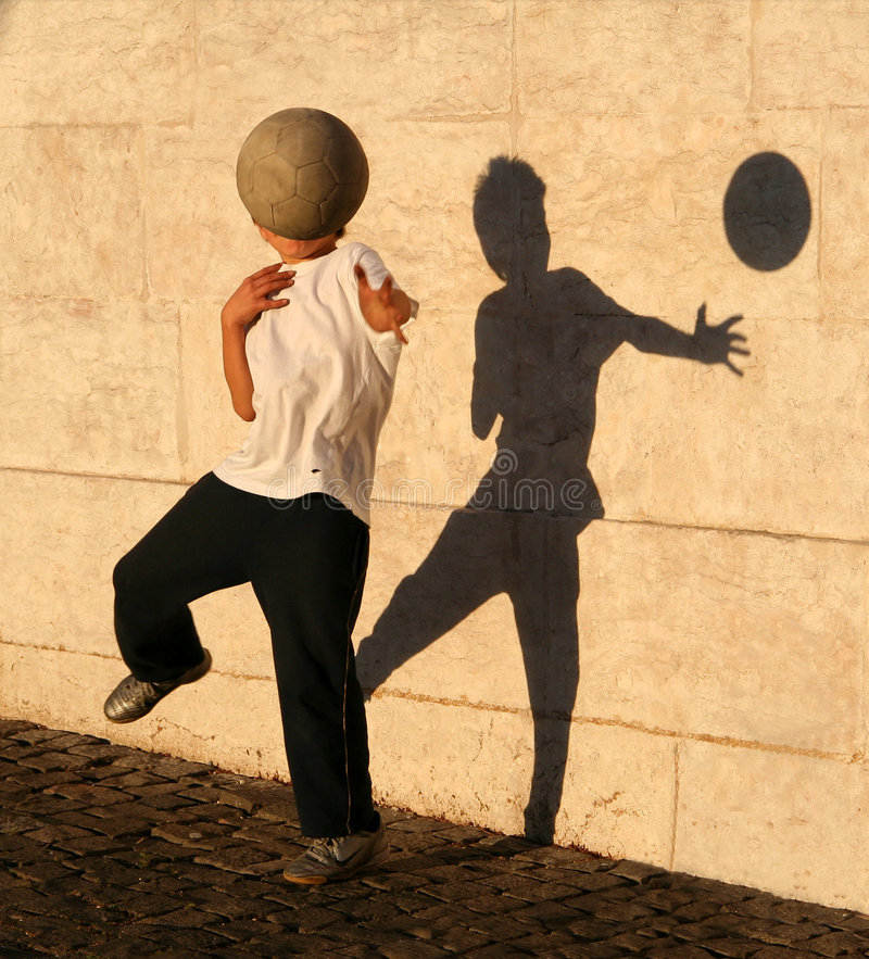 Boy playing catch with his shadow stock photography