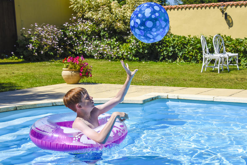 Boy playing catch in swimming pool stock photos