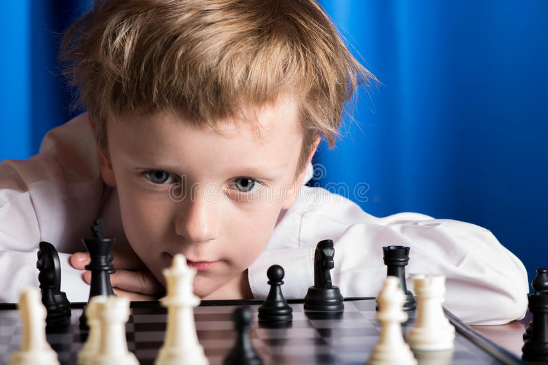 Boy playing chess. Boy in white shirt playing chess on a blue background royalty free stock images