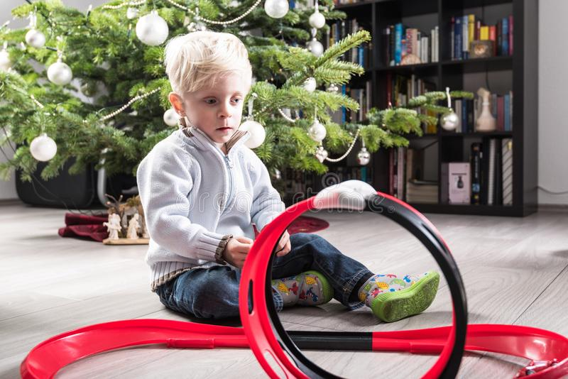Boy playing with Christmas present. Boy playing with his Christmas present, a plastic racetrack in front of the Christmas tree royalty free stock photography