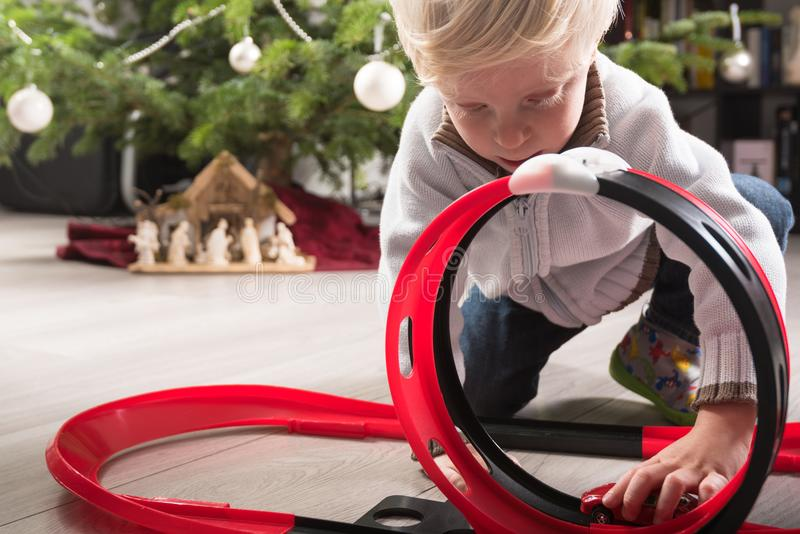 Boy playing with Christmas present. Boy playing with his Christmas present, a plastic racetrack in front of the Christmas tree stock images