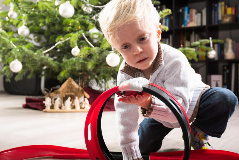 Boy playing with Christmas present. Boy playing with his Christmas present, a plastic racetrack in front of the Christmas tree stock photo