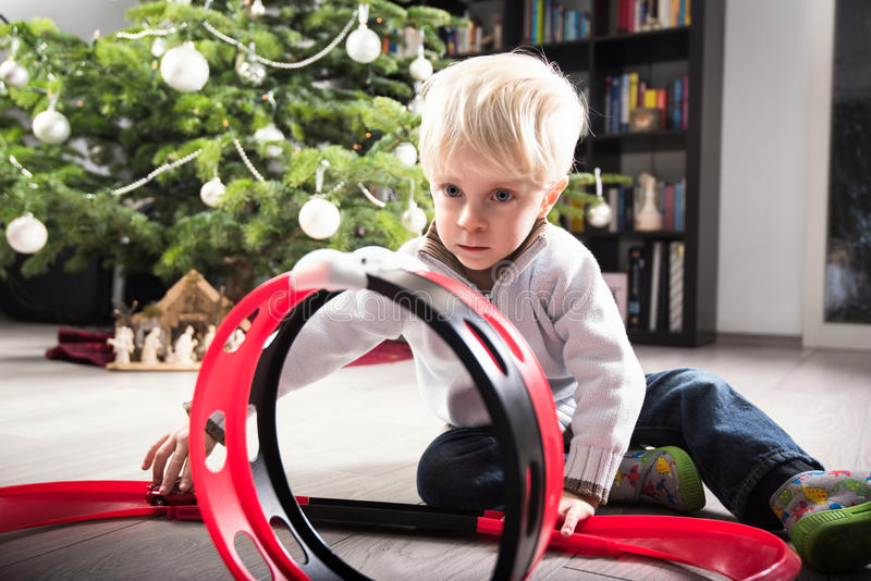 Boy playing with Christmas present. Boy playing with his Christmas present, a plastic racetrack in front of the Christmas tree royalty free stock photo