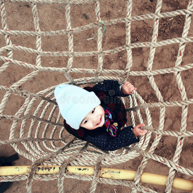 Boy playing on climbing frame royalty free stock photography