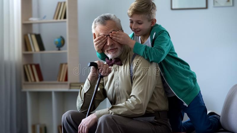 Boy playing and closing grandfather eyes, having fun together on weekends royalty free stock images