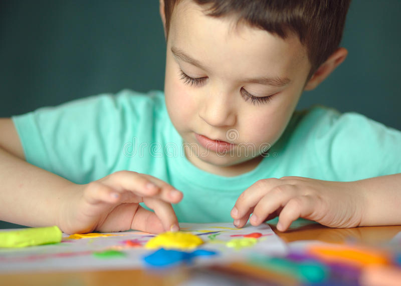 Boy playing with color play dough royalty free stock image