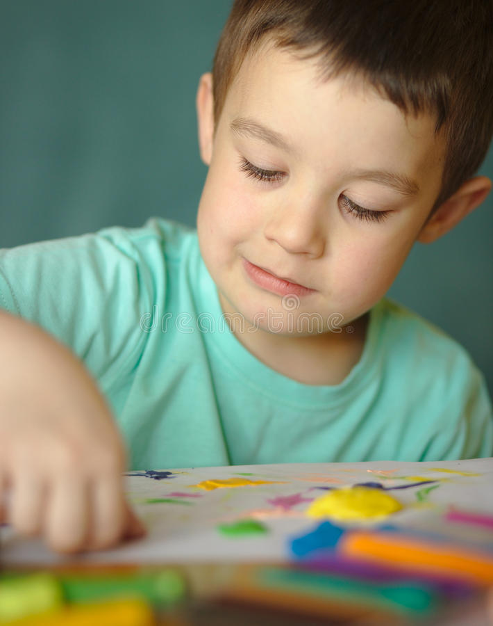 Boy playing with color play dough royalty free stock photo