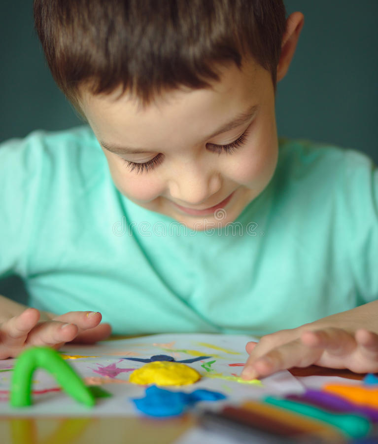 Boy playing with color play dough stock image