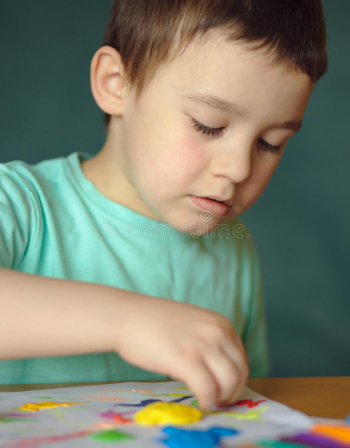 Boy playing with color play dough stock photography