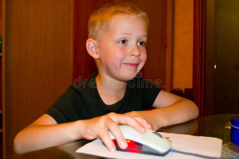Boy playing on the computer. Portrait of a Boy enthusiastically playing a computer stock photo