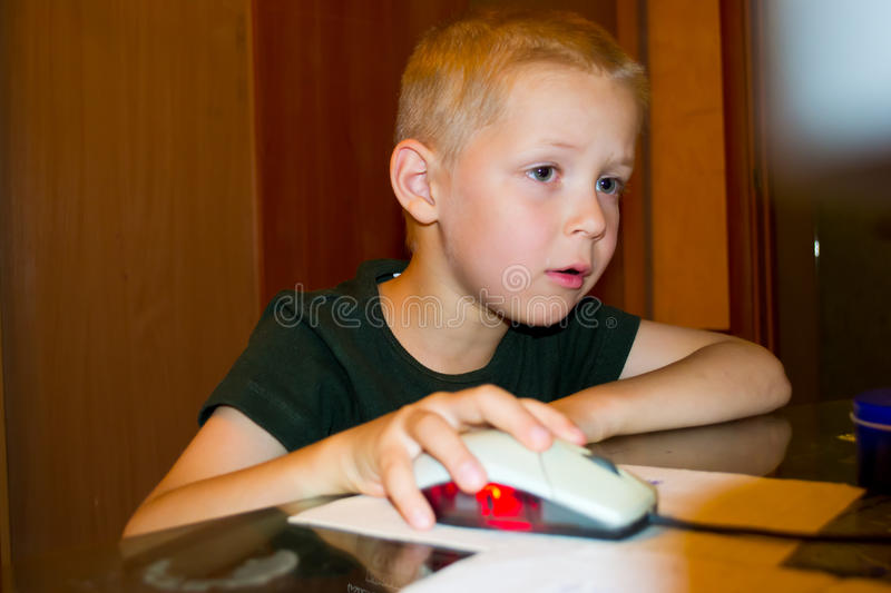 Boy playing on the computer. Portrait of a Boy enthusiastically playing a computer royalty free stock images