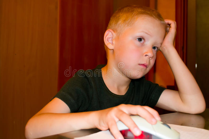 Boy playing on the computer. Portrait of a Boy enthusiastically playing a computer royalty free stock photography