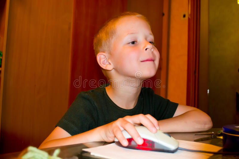 Boy playing on the computer. Portrait of a Boy enthusiastically playing a computer stock photos