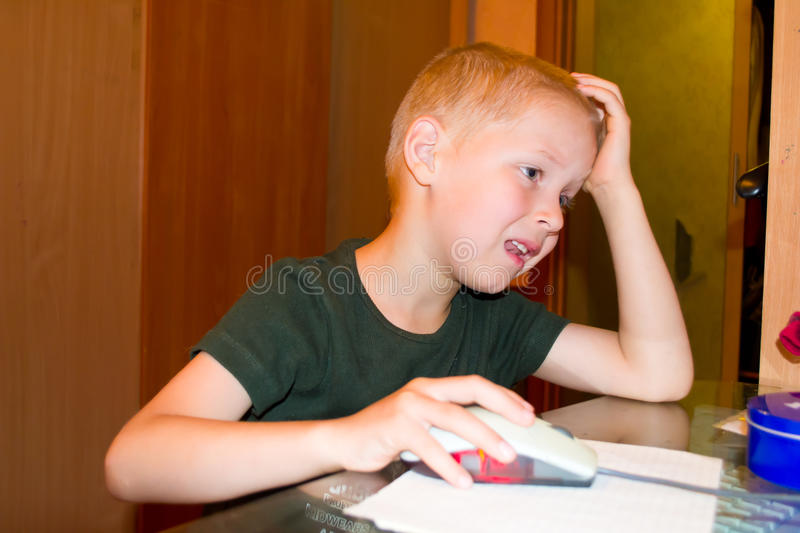 Boy playing on the computer. Portrait of a Boy enthusiastically playing a computer stock image