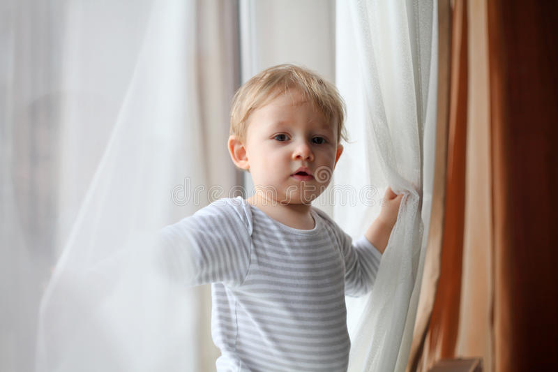 Boy playing with curtains stock image