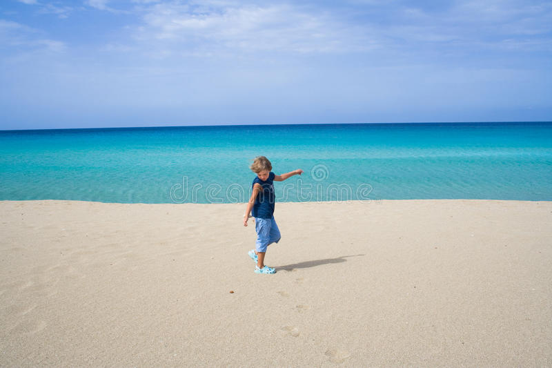 Boy playing and dancing in the ocean on a tropical beach stock image