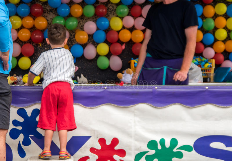 Boy playing darts carnival game. Young boy throwing darts at a carnival trying to pop balloons royalty free stock photo