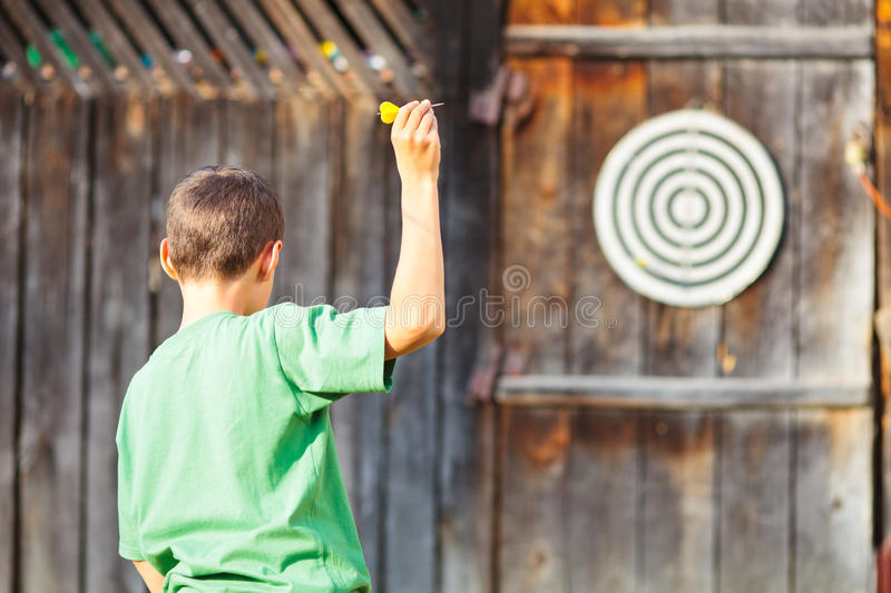 Boy playing darts outdoor. Young boy in green t-shirt playing darts outdoor stock images