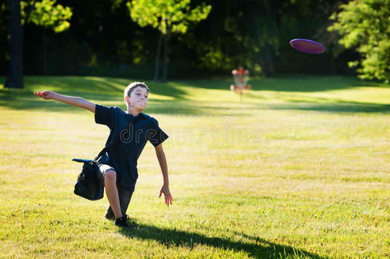 Boy playing disc golf. Young boy playing disc golf in a park on a summer day royalty free stock photography