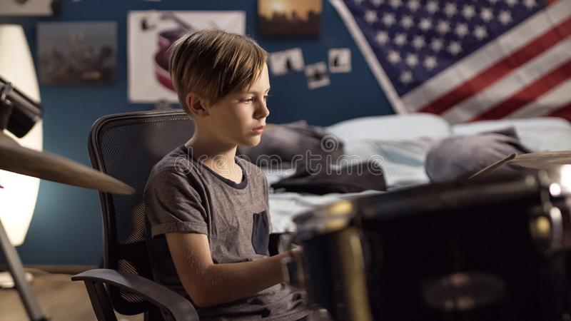 Boy playing drums in bedroom royalty free stock photo