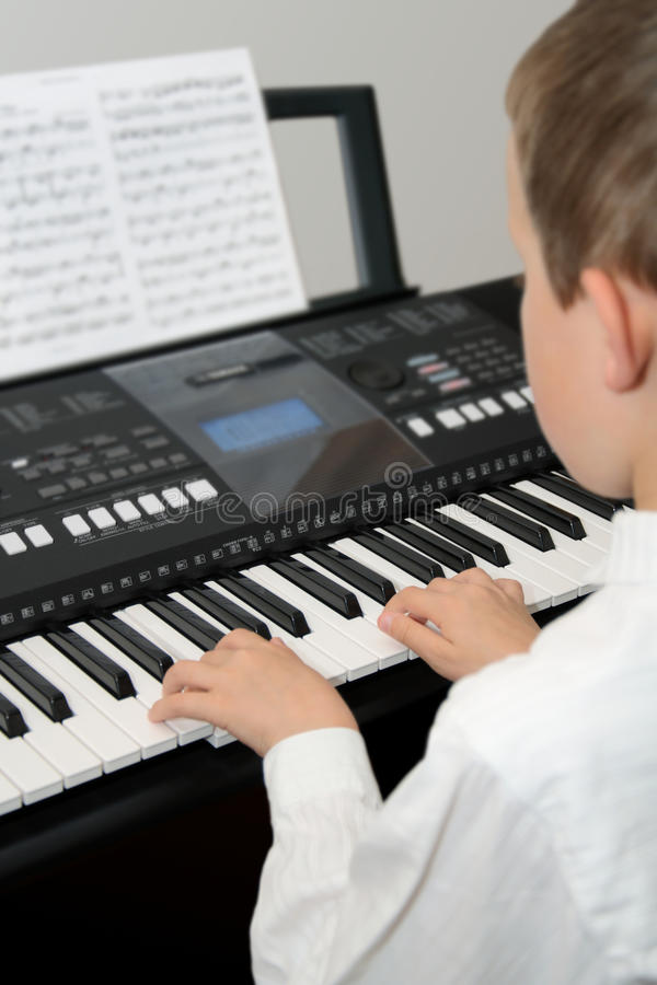 Boy playing electric piano from note sheet royalty free stock images