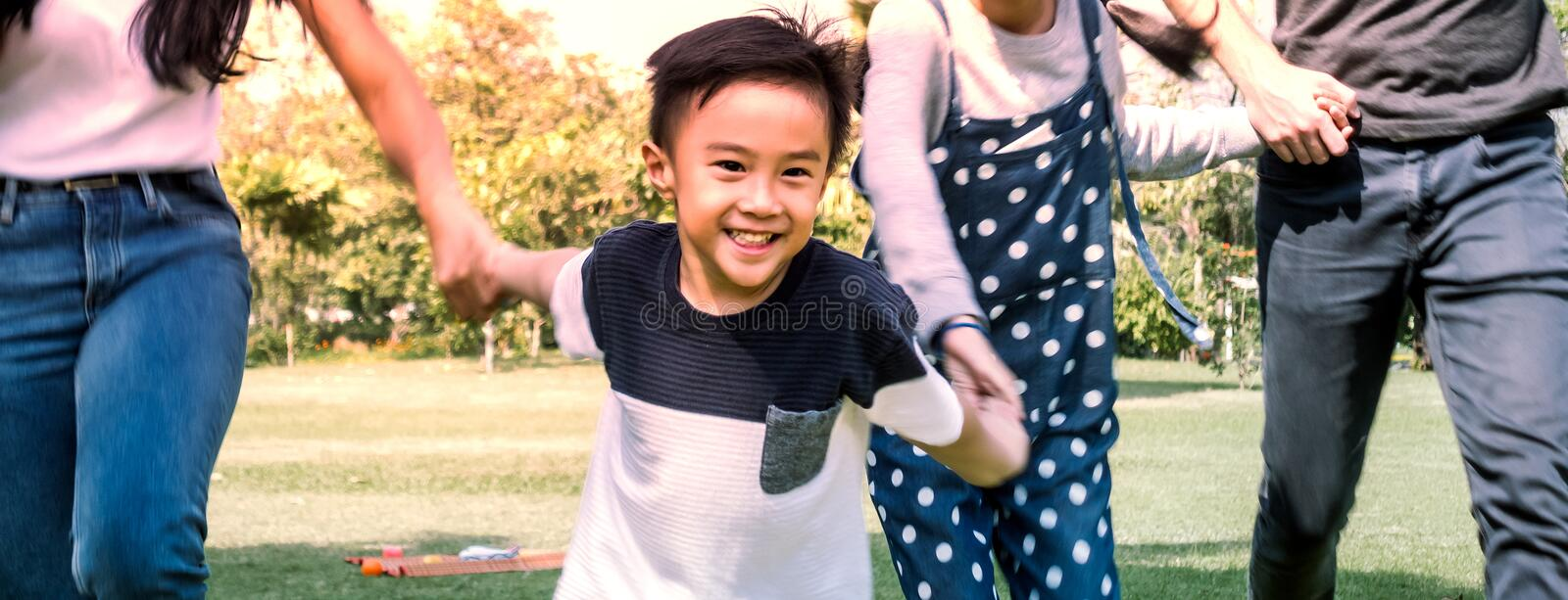 Boy playing with family having fun in summer park. stock photography